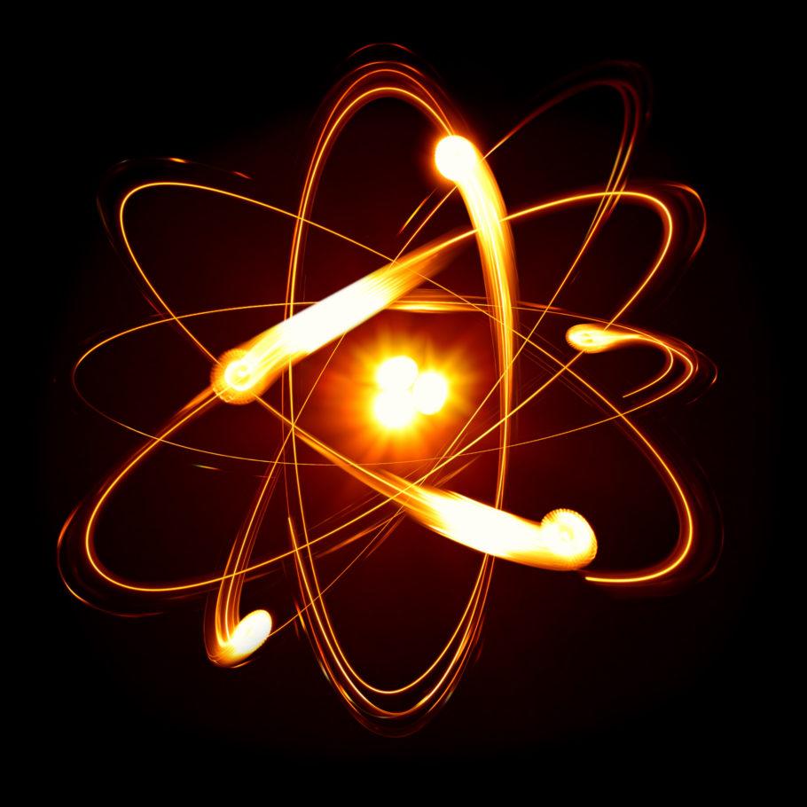 Um átomo desenhado com seu núcleo incandescente e elétrons girando em diferentes planos da eletrosfera.